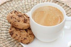 Galletas de viruta de chocolate en el platillo con café Imágenes de archivo libres de regalías