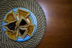 Galletas del atasco del ar?ndano y del albaricoque de Hamantash Purim en placa coloreada con el fondo de madera de la tabla foto de archivo