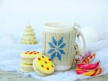 Galletas del bocadillo con la formación de hielo amarilla asperjada con las estrellas del azúcar y la taza de té en fondo de made Fotos de archivo libres de regalías