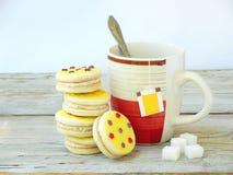 Galletas del bocadillo con la formación de hielo amarilla asperjada con las estrellas del azúcar y la taza de té Foto de archivo libre de regalías