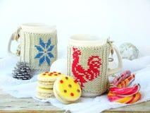 Galletas del bocadillo con la formación de hielo amarilla asperjada con las estrellas del azúcar y la taza de té La Navidad y Año Fotografía de archivo