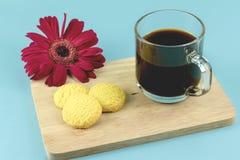 Galletas del café y de mantequilla de la mañana con el gerbera rojo en backg azul foto de archivo