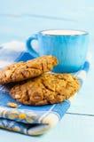 Galletas del cereal y taza de leche en una superficie de madera azul Fotos de archivo