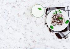 Galletas del chocolate y un vidrio de leche en el fondo blanco Visión superior Imagen de archivo libre de regalías