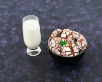 Galletas del chocolate y un vidrio de leche en fondo oscuro Fotografía de archivo