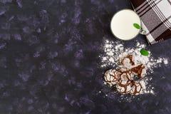 Galletas del chocolate y un vidrio de leche en fondo oscuro Visión superior Fotos de archivo libres de regalías