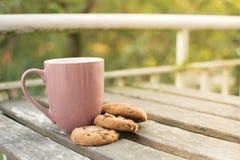 Galletas del chocolate y una taza de leche en una tabla de madera foto de archivo libre de regalías