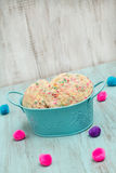 Galletas del confeti en lata azul con las bolas decorativas coloridas foto de archivo libre de regalías