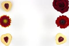 Galletas del corazón del día del ` s de la tarjeta del día de San Valentín con las flores Foto de archivo