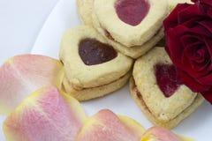Galletas del corazón del día del ` s de la tarjeta del día de San Valentín con los pétalos color de rosa Foto de archivo