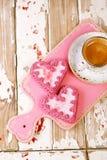 Galletas del corazón y taza de café rojas del café express en la tabla de madera vieja Imagen de archivo libre de regalías