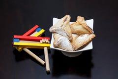 Galletas del día de fiesta de Purim, Ozne Haman en noisemaker hebreo y colorido foto de archivo libre de regalías