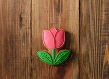 Galletas del día de fiesta que hielan el fondo de madera rojo del tulipán de la flor foto de archivo libre de regalías