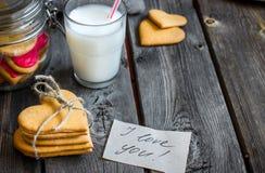 Galletas del día de tarjetas del día de San Valentín y vidrio en forma de corazón de leche foto de archivo libre de regalías