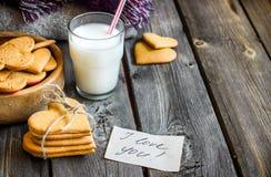 Galletas del día de tarjetas del día de San Valentín y vidrio en forma de corazón de leche fotos de archivo libres de regalías