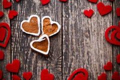 Galletas del jengibre de la forma del corazón en la tabla de madera Fotos de archivo libres de regalías