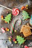 Galletas del jengibre de la Navidad, bastón, piruleta y caramelo dulce derramados con nieve Fotos de archivo libres de regalías