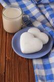 Galletas del jengibre en la forma del corazón en un platillo y una taza de chocolate caliente en una tabla de madera Foto de archivo