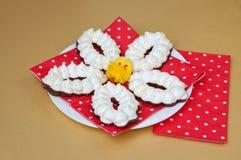 Galletas del merengue de Pascua en una placa blanca con una servilleta roja Foto de archivo