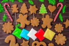 Galletas del pan de jengibre, copos de nieve, árbol de navidad, campana, hombre, colgando con la cinta sobre un fondo de madera d Fotos de archivo