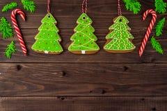 Galletas del pan de jengibre, copos de nieve, árbol de navidad, campana, hombre, colgando con la cinta sobre un fondo de madera d Imagenes de archivo