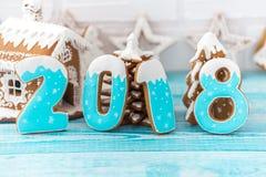 Galletas del pan de jengibre, copos de nieve que cuelgan con la cinta sobre un fondo de madera azul Copyspace del espacio libre p Fotografía de archivo libre de regalías