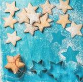 Galletas del pan de jengibre de la Navidad asperjadas con el polvo del azúcar en fondo azul Imagen de archivo libre de regalías
