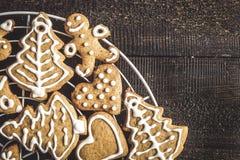 Galletas del pan de jengibre de la Navidad con la formación de hielo en fondo oscuro con Imagen de archivo libre de regalías
