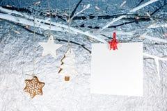 Galletas del pan de jengibre de la Navidad con la tarjeta de felicitación vacía que cuelga o Foto de archivo libre de regalías
