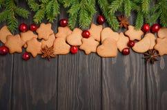 Galletas del pan de jengibre de la Navidad Concepto del día de fiesta adornado con las ramas y los arándanos del abeto Foto de archivo libre de regalías