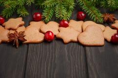 Galletas del pan de jengibre de la Navidad Concepto del día de fiesta adornado con las ramas y los arándanos del abeto Fotografía de archivo libre de regalías