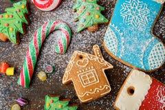 Galletas del pan de jengibre de la Navidad y bastón dulce derramados con nieve Fotos de archivo libres de regalías