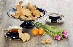 Galletas del pan de jengibre de Pascua y taza de té hechas en casa Foto de archivo