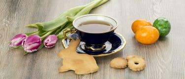 Galletas del pan de jengibre de Pascua y taza de té hechas en casa Imágenes de archivo libres de regalías