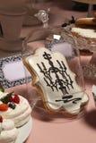 Galletas del pan de jengibre en el bulbo de cristal en la tabla ligera del fondo con las tortas Foto de archivo libre de regalías