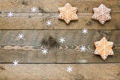 Galletas del pan de jengibre en fondo de madera con los copos de nieve con el espacio para su texto foto de archivo libre de regalías
