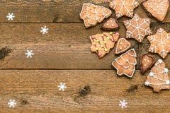 Galletas del pan de jengibre en fondo de madera con los copos de nieve con el espacio para su texto Fotos de archivo libres de regalías