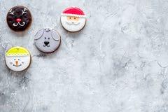 Galletas del pan de jengibre en formas de santa, de ciervos, del perro y del muñeco de nieve en copyspace gris de la opinión supe Fotos de archivo libres de regalías
