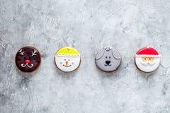 Galletas del pan de jengibre en formas de santa, de ciervos, del perro y del muñeco de nieve en copyspace gris de la opinión supe Foto de archivo libre de regalías