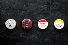 Galletas del pan de jengibre en formas de santa, de ciervos, del perro y del muñeco de nieve en copyspace negro de la opinión sup Foto de archivo libre de regalías