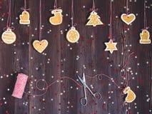 Galletas del pan de jengibre en la cuerda para la decoración del árbol de navidad con las tijeras y el Año Nuevo del hilo en la t Foto de archivo