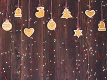 Galletas del pan de jengibre en la cuerda por Año Nuevo de la decoración del árbol de navidad en la tabla de madera Fotografía de archivo libre de regalías
