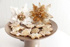 Galletas del pan de jengibre en una placa con adornos de la Navidad Imagen de archivo