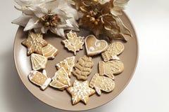 Galletas del pan de jengibre en una placa con adornos de la Navidad Foto de archivo