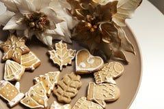 Galletas del pan de jengibre en una placa con adornos de la Navidad Fotografía de archivo libre de regalías