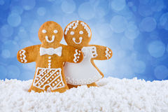 Galletas del pan de jengibre, hombres de pan de jengibre en la nieve en el fondo azul, tarjeta de felicitación de la plantilla Foto de archivo libre de regalías