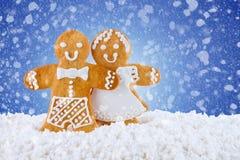 Galletas del pan de jengibre, hombres de pan de jengibre en la nieve en el fondo azul, tarjeta de felicitación de la plantilla Imagen de archivo