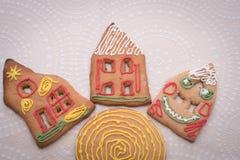 Galletas del pan de jengibre de la Navidad con la forma de la casa en la tabla Imagen de archivo