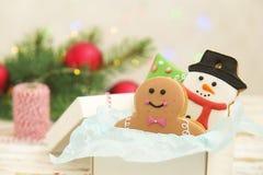 Galletas del pan de jengibre de la Navidad en el cierre de madera blanco del fondo de la caja de regalo para arriba Foto de archivo