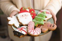 Galletas del pan de jengibre de la Navidad en la placa en las manos del ` s de las mujeres Foto de archivo libre de regalías